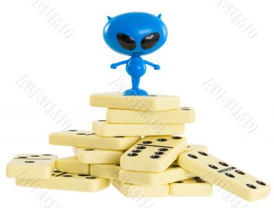 Blue toy alien on a heap from dominoes