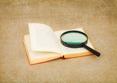 Old book and magnifier glass on canvas