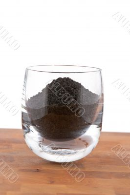 black onion seeds in glass on wooden table