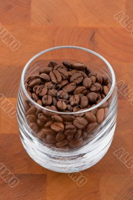 coffea beans in glass on wooden table