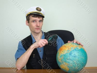 Guy in a sea uniform cap with globe and magnifier