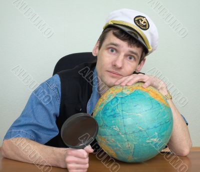 Man in a sea uniform cap with globe and magnifier