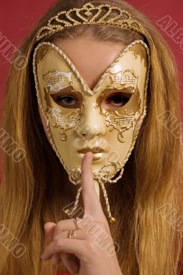 young woman in mask shows gesture of silence