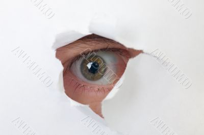 Human eye looking through a hole in paper