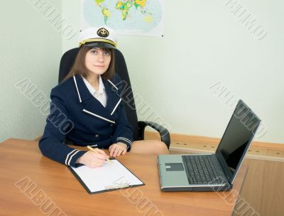Girl in a sea uniform at office with laptop and tablet