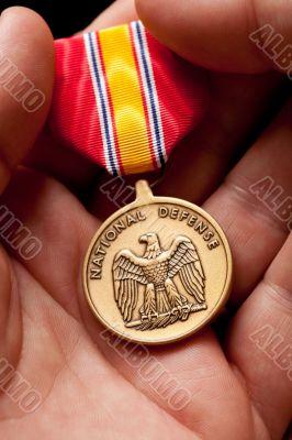 Man Holding National Defense War Medal