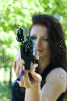 Woman aiming pneumatic gun