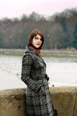 dark hair girl near river bank looking appear