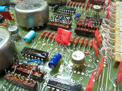 old circuit board from the 80th with colored electronic pieces