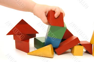 The children`s hand has destroyed construction from cubes