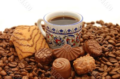 Cup of coffee with cookies and chocolates