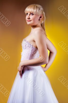 young blonde in wedding dress turned back