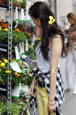 Young woman buying flowers on the market.