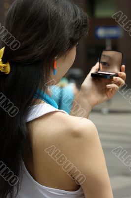 Young Woman with a lipstick mirror on the road.