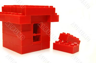 Small house constructed of red toy blocks