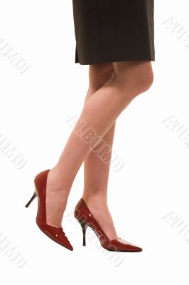 Woman`s legs wearing red shoes
