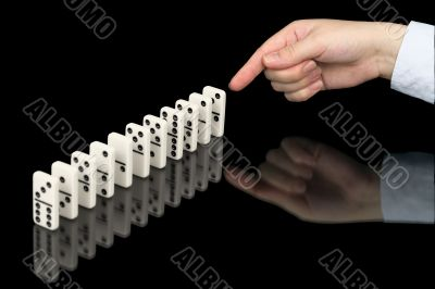 Hand pushing dominoes counters on black