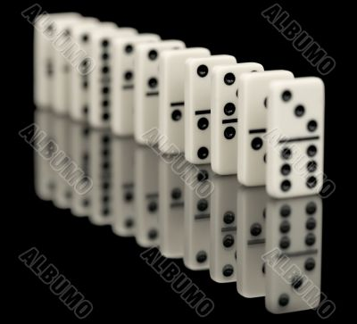 Some bones of dominoes put abreast on a black