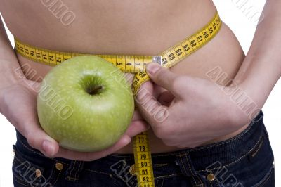 Waist is 65.5. Woman with measure tape and apple