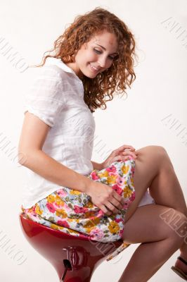 Young woman sitting on a stool