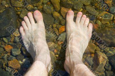 bare feet on shoal of lake