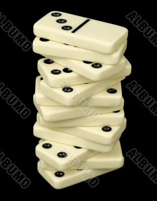 Tower from dominoes bones on a black