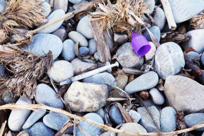 Used syringe on pebbles