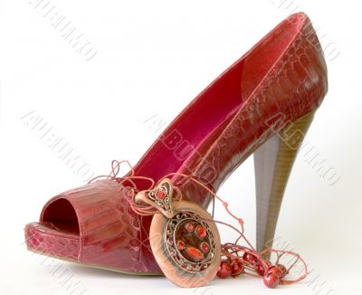 Red shoe with high heel and necklace