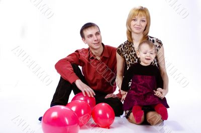 family of three people. with a small child and balls