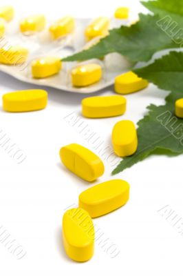 yellow vitamin pills and green leaves