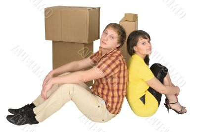Guy and the girl sit near boxes