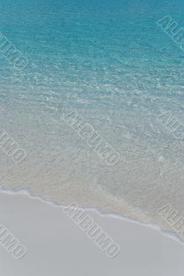 Gentle surf. White sand beach