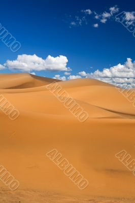 sand dunes and cumulus clouds