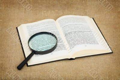 Open book and magnifier against a canvas - a still-life