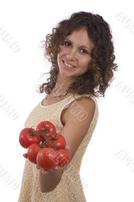 Smiling woman holding branch of red tomatoes