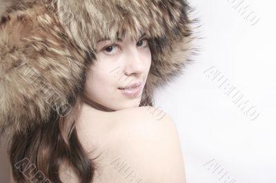 Portrait of the beautiful girl in a fur cap .