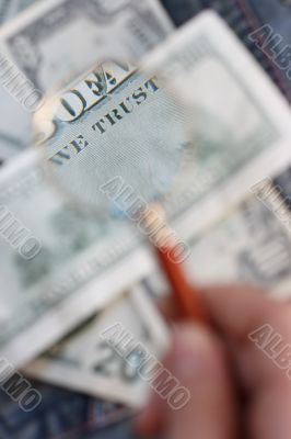 100 USD  banknote is under  a magnifying glass