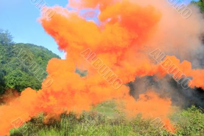 Orange smoke above a mountain glade