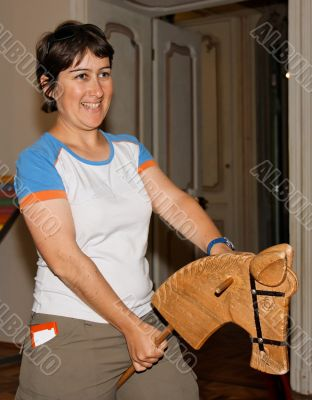 Smiling woman riding a hobby-horse