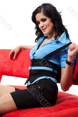 Brunette woman sittin on red sofa