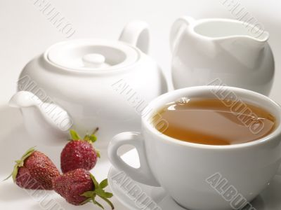 cup of black tea on the table with dishware and strawberry