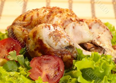 grilled chicken, whole with vegetables on salad leafs