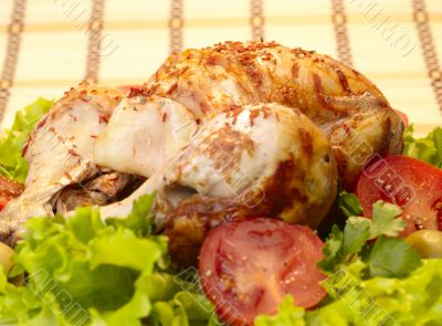grilled chicken whole with vegetables on salad leafs