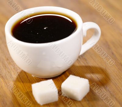 Espresso cup with pair of sugar on the wooden table