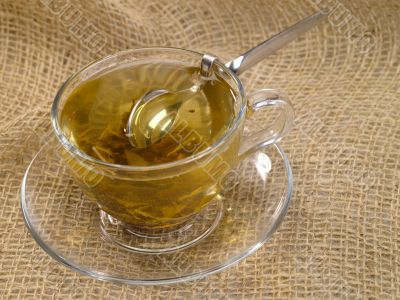 cup of green tea on hessian with honey spoon