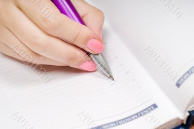 Hand writing in a notebook with pen