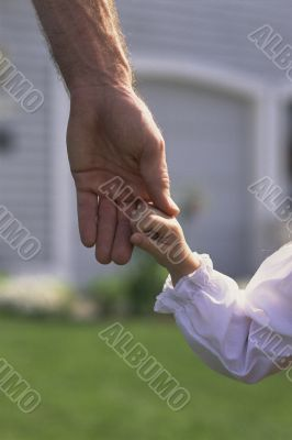 Father Daintily Holding Tiny Hand of Daughter
