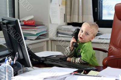 Little boy speaking on phone in the office