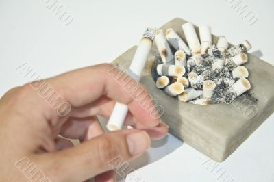 Full ashtray and hand holding cigarette