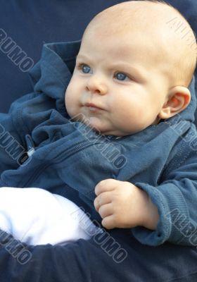 Small newborn baby in blue jacket